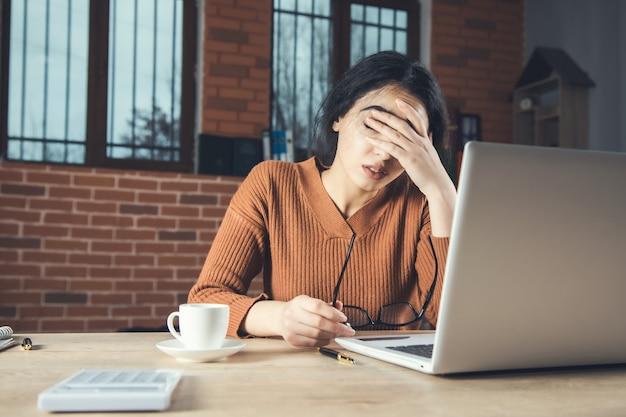 Грустная женщина, работающая в компьютере в офисе
