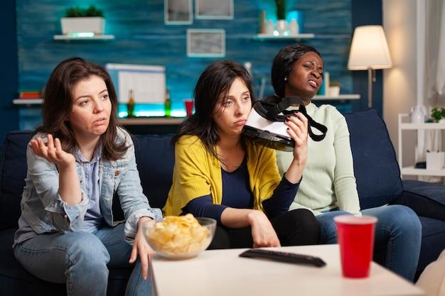 ソファに座ってvrヘッドセットを保持しているバーチャルリアリティゲームの競争を失った後の悲しい女性。居間で夜遅く楽しんで一緒にぶらぶらしている人々の混血グループ