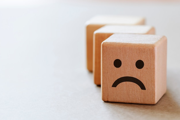 Sad wooden dices with unhappy face