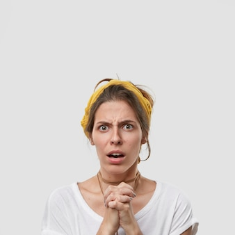 Sad worried puzzled woman poses in praying gesture, asks for apology, has discontent facial expression