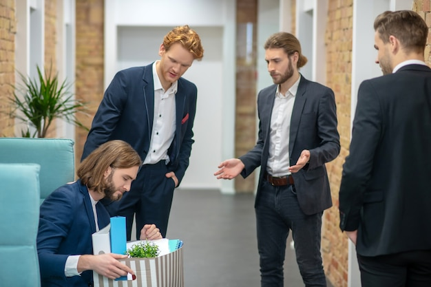 Sad young adult man sitting with box and three empathic colleagues standing in office