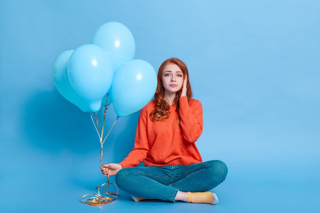 Sad young adult sitting on floor with crossed legs holding bunch of balloons in hand, looks at front
