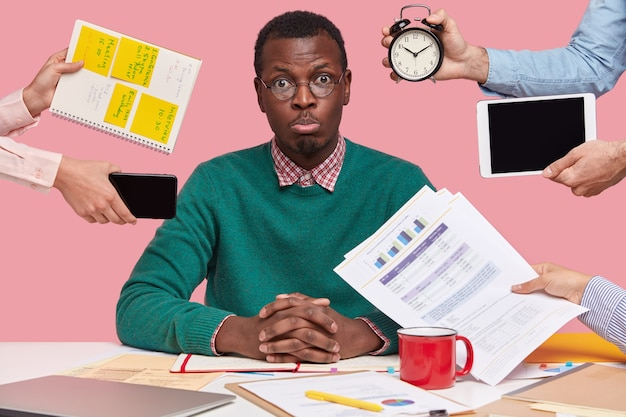 Sad young african american man dressed in green sweater, sits at desktop, hands with papers, alarm clock, touchpad, notepad with stickes