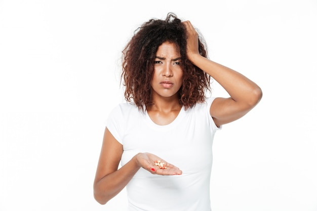 Sad young african lady holding pills with headache.