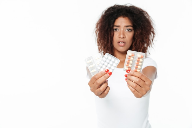Sad young african lady holding pills.