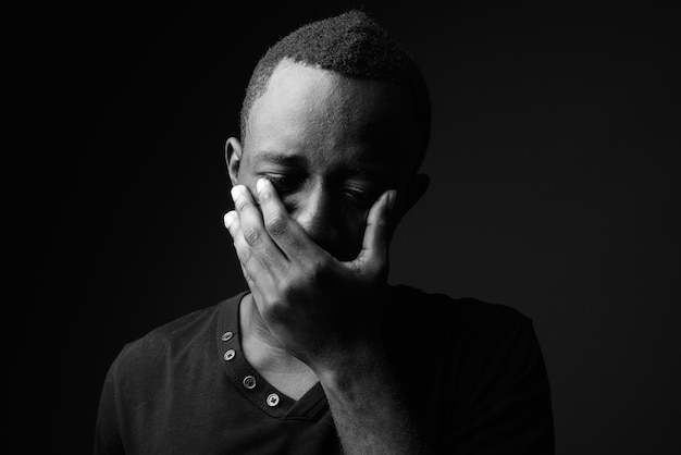Sad young african man against black wall in black and white