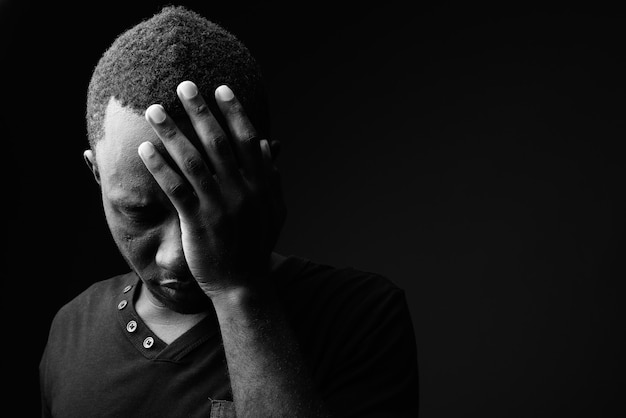 Sad young african man looking stressed in black and white