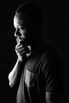 Sad young african man profile view thinking in black and white