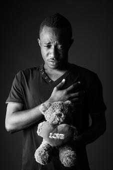 テディベアと黒と白の愛のサインテキストを持つ悲しい若いアフリカ人
