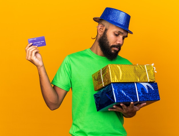 Sad young afro-american guy wearing party hat holding gift boxes with credit card
