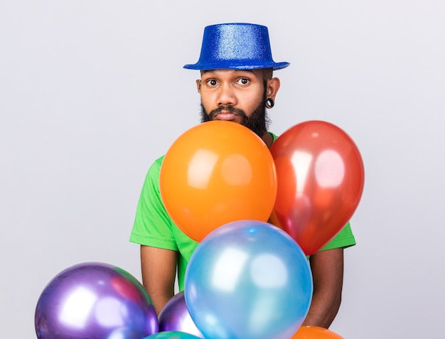 Sad young afro-american guy wearing party hat standing behind balloons isolated on white wall