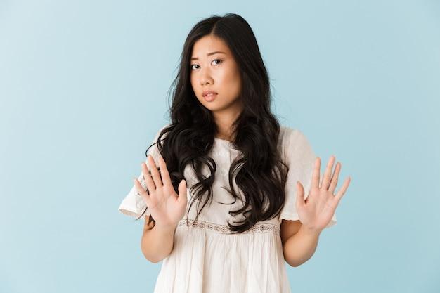 Грустная молодая азиатская красивая женщина позирует изолированной над синей стеной, делает стоп-жест