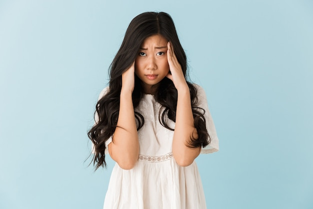 Sad young asian beautiful woman with headache isolated over blue wall