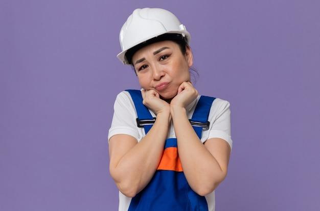 흰색 안전 헬멧을 쓴 슬픈 젊은 아시아 건축업자 여성이 얼굴에 손을 대고 바라보고 있다