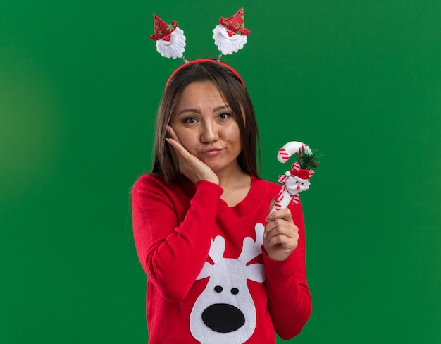 Грустная молодая азиатская девушка в рождественском обруче для волос со свитером, держащим рождественские конфеты, положив руку на щеку, изолированную на зеленом фоне