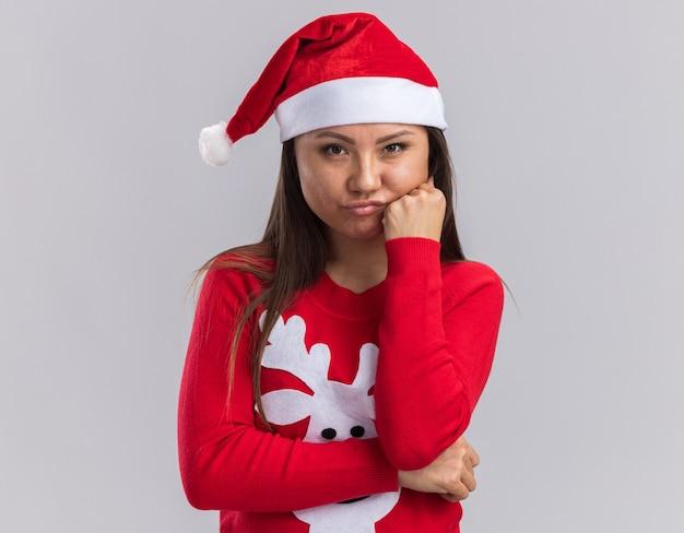 Грустная молодая азиатская девушка в новогодней шапке со свитером, положив руку на щеку, изолированную на белом фоне