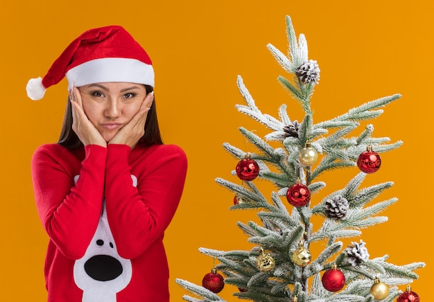 Sad young asian girl wearing christmas hat with sweater standing nearby christmas tree putting hands on cheeks isolated on orange background