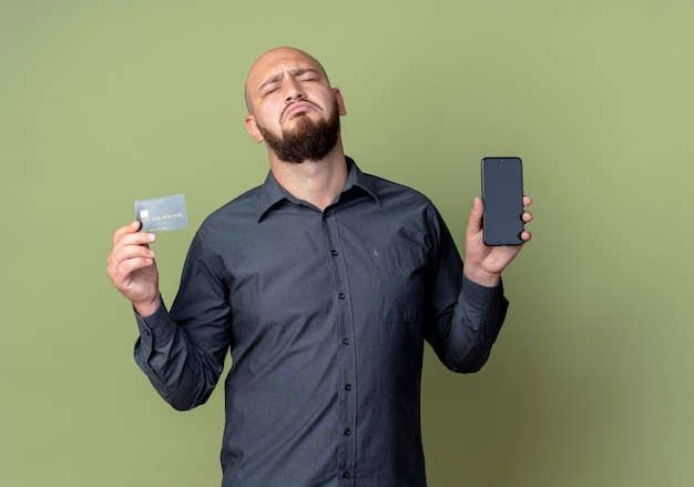 Sad young bald call center man holding mobile phone and credit card with closed eyes isolated on olive green wall