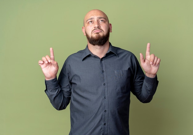 Sad young bald call center man looking and pointing up isolated on olive green wall