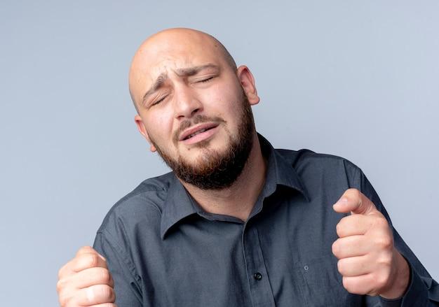 Uomo calvo giovane triste del call center con i pugni chiusi e gli occhi chiusi isolati sulla parete bianca