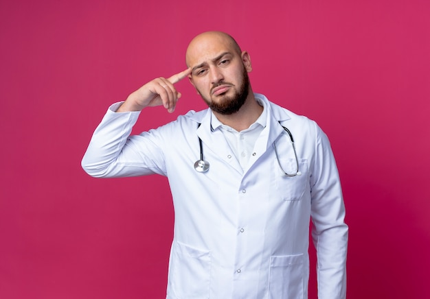 Sad young bald male doctor wearing medical robe and stethoscope putting finger on forehead isolated on pink