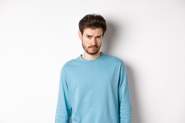 Sad young bearded man sulking, looking upset at camera, offended by someone, standing against white background.
