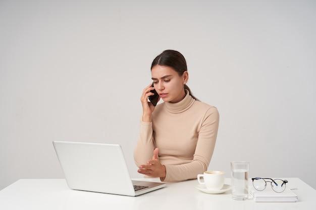Triste giovane bella donna castana avendo una conversazione tesa e alzando confusamente la mano mentre si lavora in ufficio con il suo laptop, avendo una tazza di caffè mentre è seduto sul muro bianco