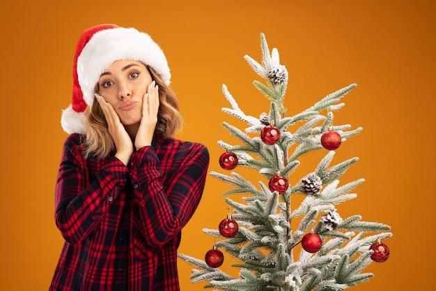 Грустная молодая красивая девушка стоит возле елки в новогодней шапке, положив руки на щеки, изолированные на оранжевом фоне