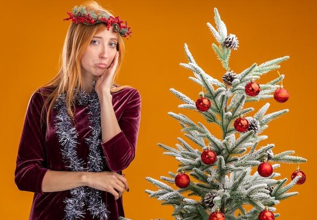 Грустная молодая красивая девушка стоит возле елки в красном платье и венке с гирляндой на шее, положив руку на щеку, изолированную на оранжевой стене