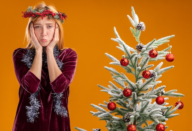 Triste giovane bella ragazza in piedi vicino all'albero di natale che indossa un abito rosso e una corona con una ghirlanda sul collo coperto il viso con le mani isolate sulla parete arancione