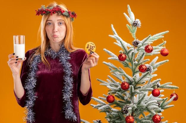 Triste giovane bella ragazza in piedi vicino all'albero di natale che indossa un vestito rosso e la corona con la ghirlanda sul collo che tiene un bicchiere di latte con i biscotti isolati su sfondo arancione