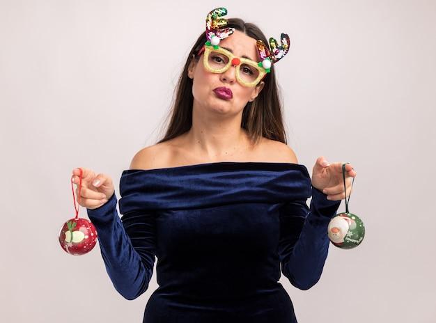 Грустная молодая красивая девушка в синем платье и рождественских очках держит елочные шары на белой стене
