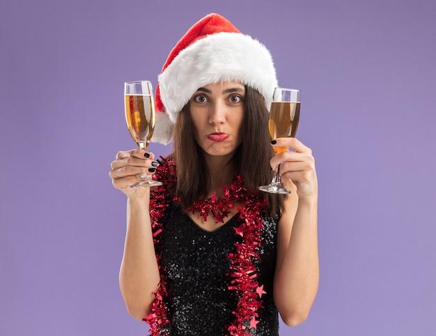 Giovane bella ragazza triste che porta il cappello di natale con la ghirlanda sul collo che tiene un bicchiere di champagne isolato su sfondo viola