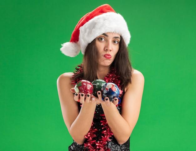 Грустная молодая красивая девушка в новогодней шапке с гирляндой на шее, протягивая елочные шары, изолированные на зеленой стене
