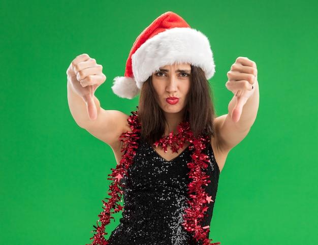 Грустная молодая красивая девушка в новогодней шапке с гирляндой на шее показывает палец вниз, изолированную на зеленой стене