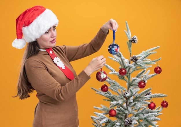 Грустная молодая красивая девушка в новогодней шапке с галстуком стоит рядом с елкой и смотрит на елочный шар на оранжевом фоне