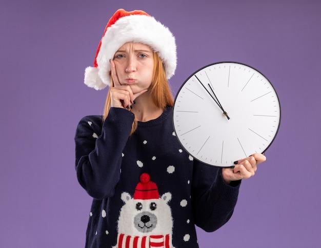 보라색 배경에 고립 된 뺨에 손을 넣어 벽 시계를 들고 크리스마스 스웨터와 모자를 입고 슬픈 젊은 아름 다운 소녀