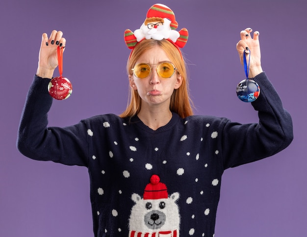 Sad young beautiful girl wearing christmas sweater and christmas hair hoop with glasses raising christmas balls isolated on purple wall