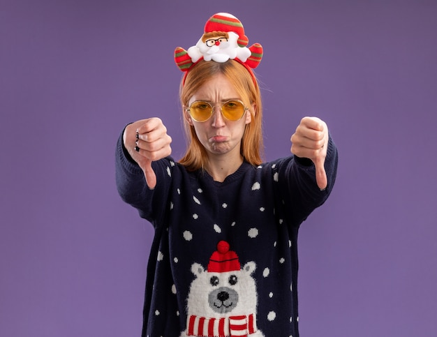 Sad young beautiful girl wearing christmas sweater and christmas hair hoop with glasses showing thumbs down isolated on purple background