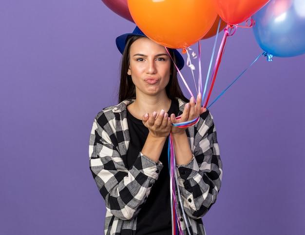 風船を保持しているパーティー帽子をかぶって悲しい若い美しい少女