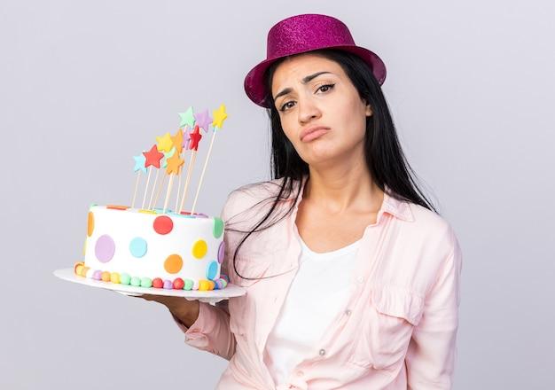 白い壁に分離されたケーキを保持しているパーティー帽子をかぶって悲しい若い美しい少女