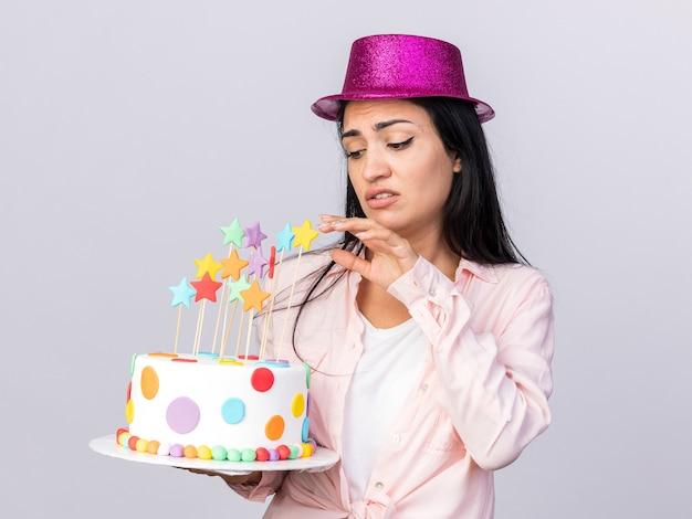 Triste giovane bella ragazza che indossa un cappello da festa che tiene e guarda la torta isolata sul muro bianco
