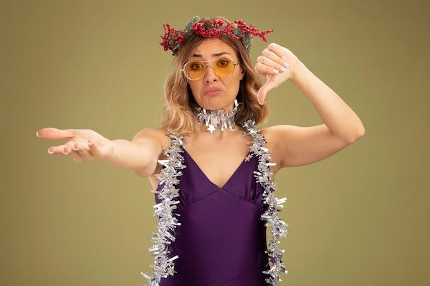 Грустная молодая красивая девушка в фиолетовом платье и очках с венком и гирляндой на шее показывает большой палец вниз, протягивая руку к камере, изолированную на оливково-зеленом фоне