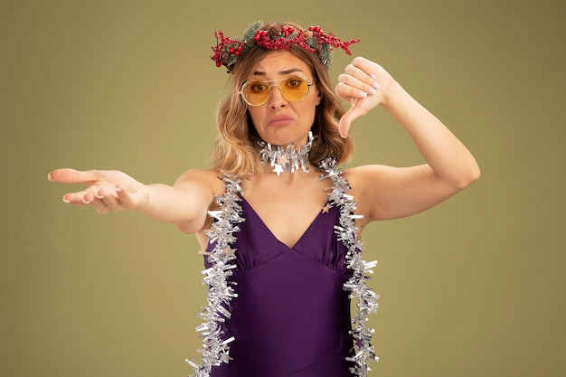 Sad young beautiful girl wearing purple dress and glasses with wreath and garland on neck showing thumb down holding out hand at camera isolated on olive green background