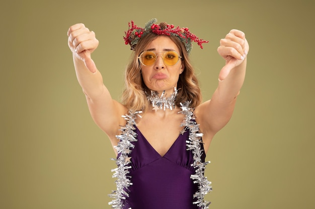Sad young beautiful girl wearing purple dress and glasses with wreath and garland on neck showing thumbs down isolated on olive green background