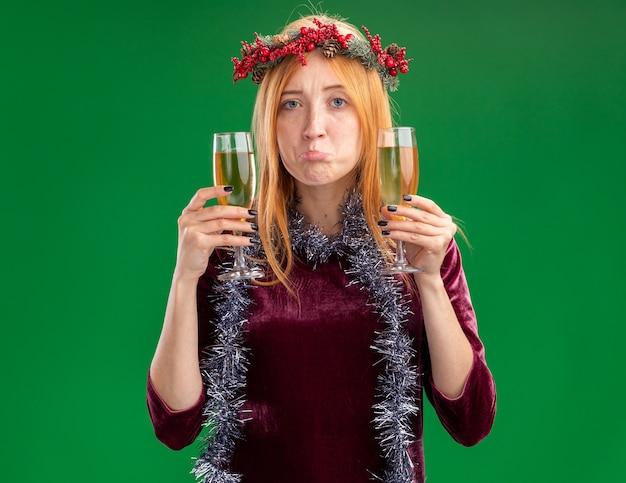 Giovane bella ragazza triste che porta vestito rosso con la corona e la ghirlanda sul collo che tiene un bicchiere di champagne isolato su priorità bassa verde