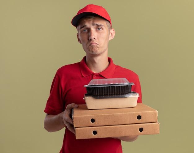 슬픈 젊은 금발 배달 소년은 복사 공간이 있는 올리브 녹색 벽에 격리된 피자 상자에 음식 패키지를 들고 있습니다