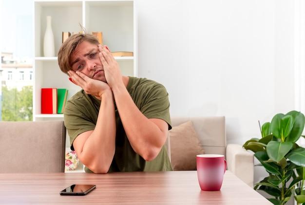 悲しい若いブロンドのハンサムな男は、顔に手を置いてカップと電話でテーブルに座っています