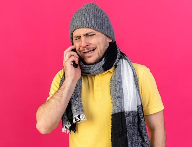 Triste giovane biondo malato uomo slavo che indossa inverno cappello e sciarpa colloqui sul telefono isolato sul colore rosa