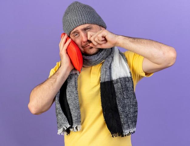 Triste giovane biondo malato uomo slavo che indossa sciarpa e cappello invernale